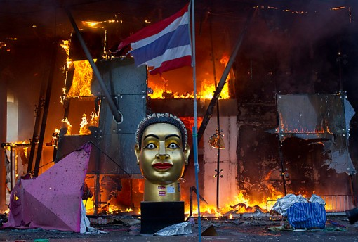 A statue of Buddha and a torn Thai national flag remain in front of Bangkok's Central World shopping mall, as it burns